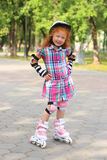 Счастливые коньки ролика маленькой девочки в лете паркуют, shallo Стоковое Изображение RF