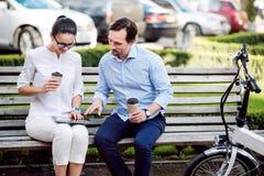 Счастливые коллеги выпивая кофе в парке Стоковая Фотография RF