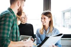 Счастливые коллеги в офисе говоря друг с другом держащ папку Стоковое Изображение