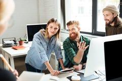 Счастливые коллеги в офисе говоря друг с другом Стоковая Фотография RF