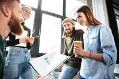 Счастливые коллеги в офисе говоря друг с другом Стоковое Изображение RF