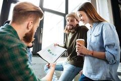 Счастливые коллеги в офисе говоря друг с другом Стоковые Изображения RF