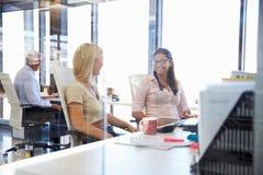 Счастливые коллеги говоря в офисе Стоковые Изображения