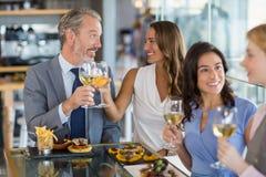 Счастливые коллеги дела взаимодействуя и провозглашать стекла пива пока имеющ обед Стоковые Фото