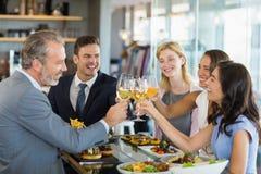Счастливые коллеги дела провозглашать стекла пива пока имеющ обед Стоковые Изображения RF