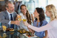 Счастливые коллеги дела провозглашать стекла пива пока имеющ обед Стоковые Фотографии RF