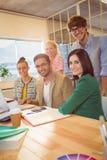 Счастливые коллеги используя компьтер-книжку в офисе Стоковая Фотография RF