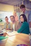 Счастливые коллеги используя компьтер-книжку в офисе Стоковые Фото