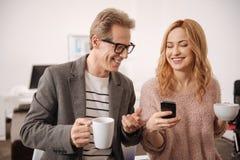 Счастливые коллеги наслаждаясь перерывом на чашку кофе в офисе Стоковая Фотография RF