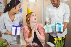 Счастливые коллеги при подарки смотря коммерсантку Стоковые Изображения