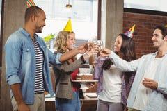 Счастливые коллеги провозглашать с шампанским в офисе Стоковые Изображения