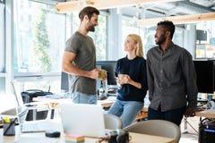 Счастливые коллеги сидя в офисе говоря друг с другом Стоковая Фотография