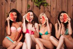 Счастливые красивые девушки в бикини есть арбуз на бассейне Стоковые Изображения RF