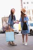 Счастливые красивые девушки идя на тротуар Стоковая Фотография