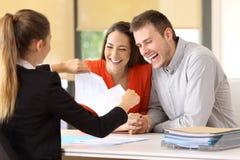 Счастливые клиенты кончая контракт и ломая его стоковое фото rf