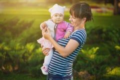 Счастливые мама и младенец в солнечном парке Стоковое фото RF
