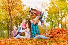 Счастливые мама и папа играют с девушками в парке осени Стоковые Изображения RF