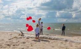 Счастливые мать и дети с красными воздушными шарами на море Стоковые Изображения RF