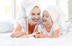 Счастливые мать и малыш семьи делают маску кожи стороны Стоковые Изображения RF