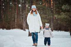 Счастливые мать и дочь на прогулке в лесе зимы Стоковая Фотография