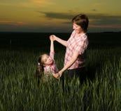 Счастливые мать и ребенок в зеленом поле на заходе солнца Стоковые Изображения RF