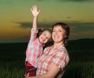 Счастливые мать и ребенок в зеленом поле на заходе солнца Стоковое Изображение RF