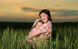 Счастливые мать и ребенок в зеленом поле на заходе солнца Стоковые Изображения