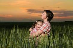 Счастливые мать и ребенок в зеленом поле на заходе солнца Стоковые Фотографии RF