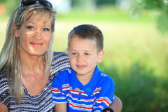 Счастливые мать и сын семьи на стенде в парке Стоковая Фотография