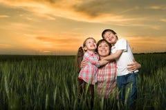 Счастливые мать и childs в зеленом поле на заходе солнца Стоковое Изображение