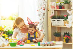 Счастливые мать семьи и девушка ребенка красят яичка для пасхи Стоковое Фото