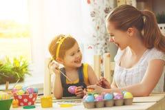 Счастливые мать семьи и девушка ребенка красят яичка для пасхи Стоковые Фото