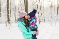 Счастливые мать семьи и дочь младенца ребенка на зиме идут в древесины Стоковые Изображения