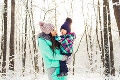 Счастливые мать семьи и дочь младенца ребенка на зиме идут в древесины Стоковые Изображения RF