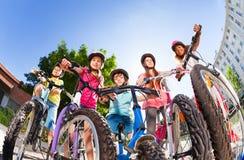 Счастливые маленькие всадники велосипеда стоя против голубого неба Стоковое Изображение RF