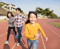 Счастливые маленькие девочки бежать на следе Стоковое Изображение RF