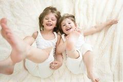 Счастливые маленькие девочки лежа на заднем взгляд сверху стоковые изображения