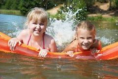 Счастливые маленькие девочки на тюфяке в озере Стоковое Изображение RF