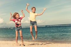 Счастливые маленькие девочки скача на пляж стоковое изображение rf