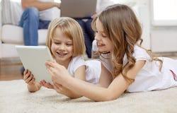 Счастливые маленькие девочки с компьютером ПК таблетки дома Стоковые Фото