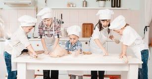 Счастливые маленькие шеф-повара подготавливая тесто в кухне Стоковая Фотография RF