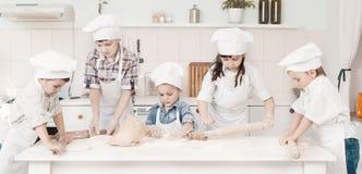 Счастливые маленькие шеф-повара подготавливая тесто в кухне Стоковая Фотография