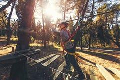 Счастливые мальчики играя на приключении паркуют держать веревочки и взбираться Стоковое Фото