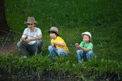 Счастливые мальчики идут удить на реке Стоковая Фотография