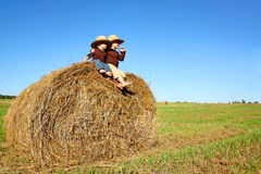 Счастливые мальчики на ферме сидя на связке сена Стоковое Изображение