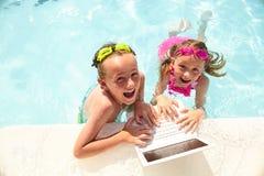 Счастливые мальчик и девушка используя компьтер-книжку в бассейне Стоковые Фотографии RF