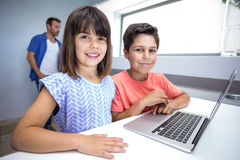 Счастливые мальчик и девушка используя компьтер-книжку Стоковое Изображение