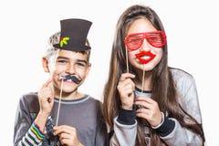 Счастливые мальчик и девушка, пробуют дальше смешные маски Стоковые Фотографии RF