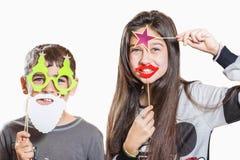 Счастливые мальчик и девушка, пробуют дальше смешные маски Стоковое фото RF