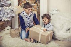 Счастливые мальчик и девушка с коробками подарков в интерьере рождества стоковое изображение